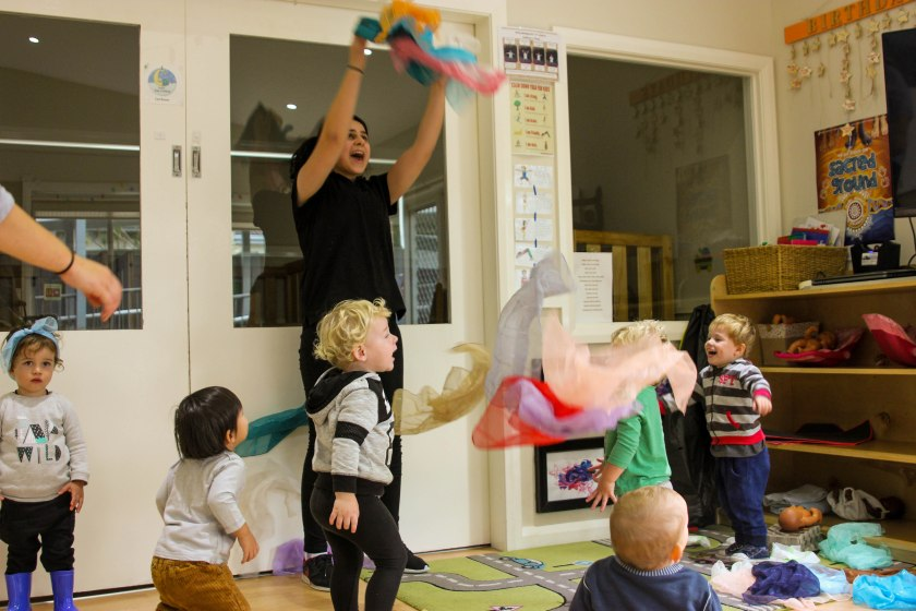 Children and educator playing indoors with fabric