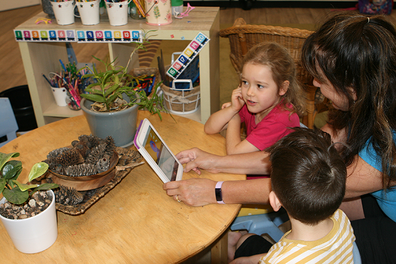 Educator and children listening to podcast on table